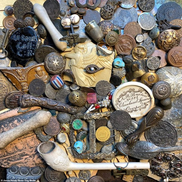 A selection of various mudlarking finds from the River Thames, London. Among them is another clay pipe, a thimble, lapel pins, coins and jewellery