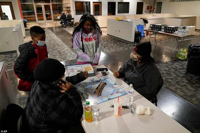 Richardson, Texas: Shaemiya Taylor, left front, and Marsha Williams, right front, play a board game as Jeremiah Murphy, left rear, and Khloee Williams, right rear, look on at a warming shelter Tuesday.In cooperation with the cities emergency management center, this location is one of seven that have opened in the city, offering those in need a place to keep warm