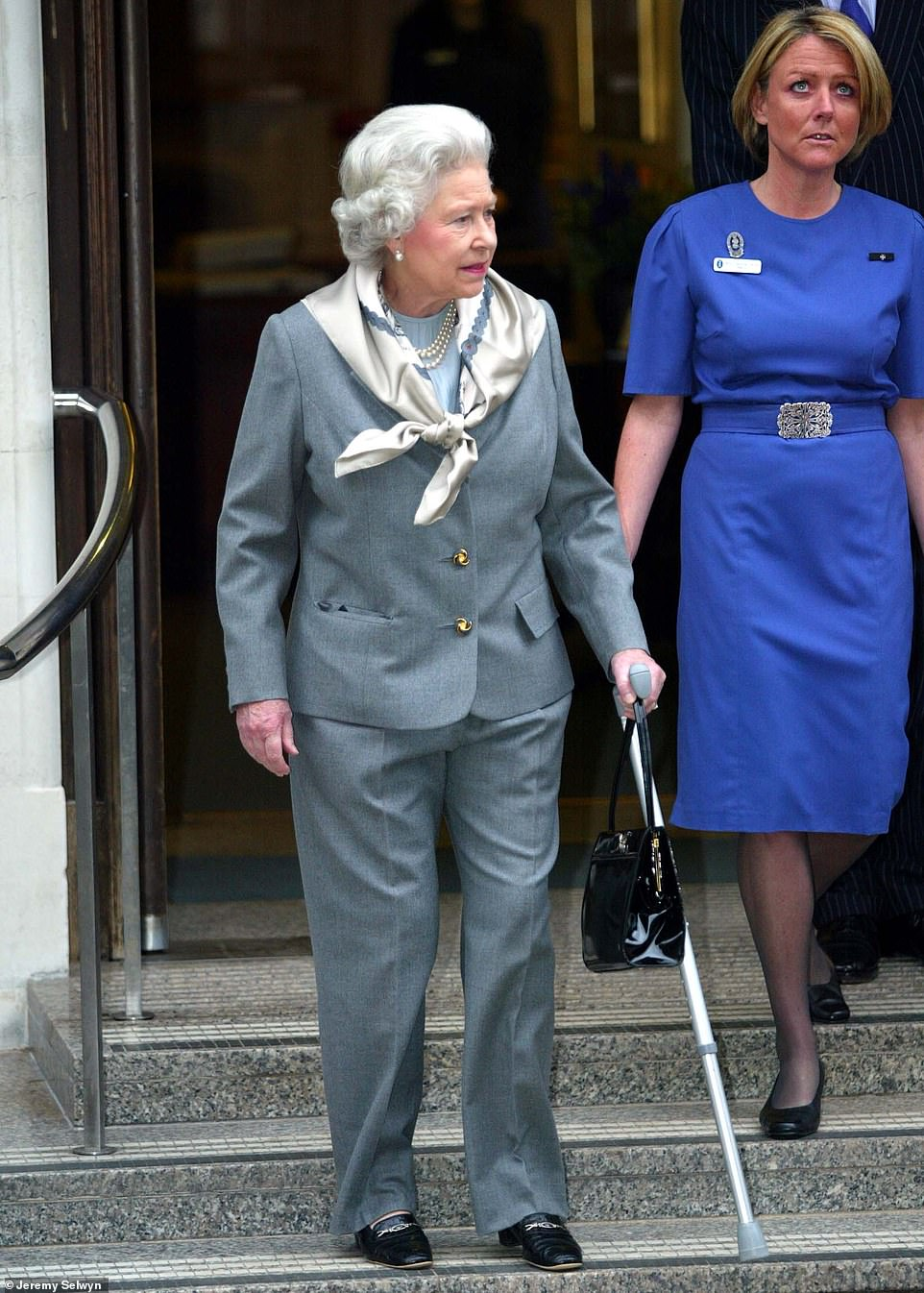 The Queen walks with a stick as she leaves King Edward VII Hospital in January 2003 after surgery to remove a torn cartilage