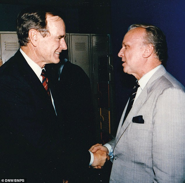 The secret medals of a CIA spy Jim Fees who managed to smuggle a Soviet MiG fighter jet into the US during the Cold War have been put up for action after they were hidden in a picture frame for decades. Pictured: Jim Fees (right) with George Bush Senior (left)