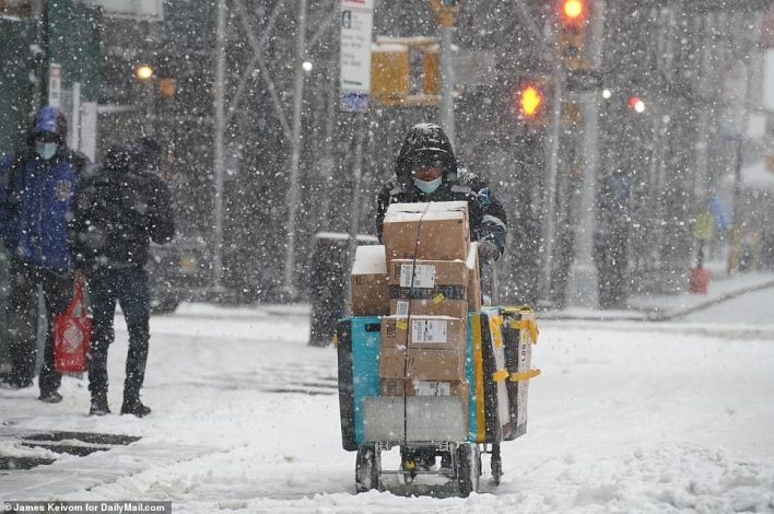 MANHATTAN, NEW YORK: A delivery person is seen pushing a cart full of packages through the snow on Thursday