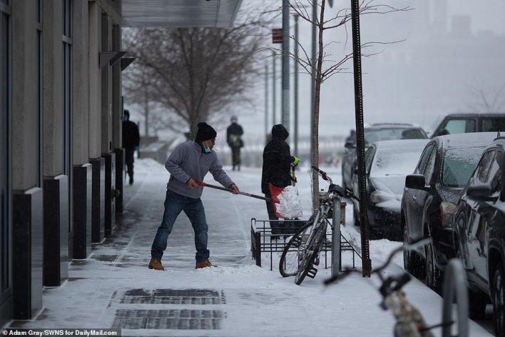 BROOKLYN, NEW YORK: A man shovels snow off the sidewalk in Williamsburg, Brooklyn, on Thursday