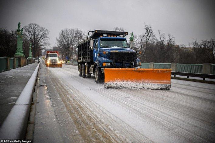 WASHINGTON, DC: Trucks clear ice and snow off the William Howard Taft Bridge in the Woodley Park neighborhood of DC, on Thursday