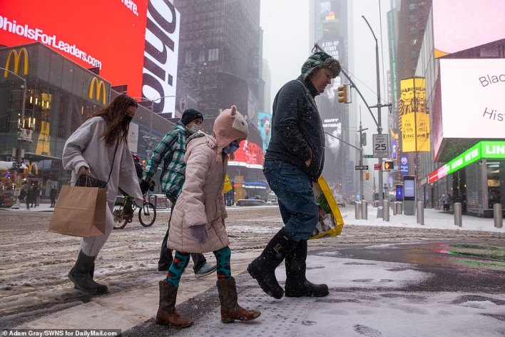 MANHATTAN, NEW YORK: 'Another wave of precipitation looks likely this evening, which could bring an additional burst of snow and sleet for central and eastern Pennsylvania, southern New York, New Jersey and Maryland,' AccuWeather Senior Meteorologist Courtney Travis said. New Yorkers are seen crossing a street in Times Square Thursday morning