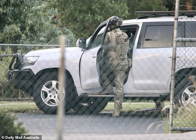 Police said on Friday morning that the situation is ongoing. Pictured are camouflaged police officers at the scene early Friday morning
