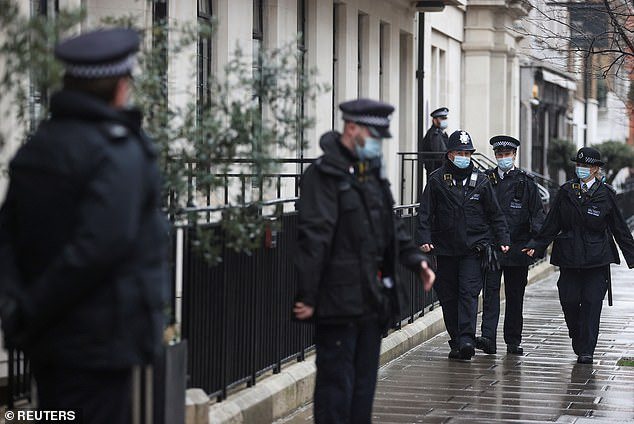 Police officers stand at the entrance of The King Edward VII hospital where Prince Philip, who turns 100 this year, is currently receiving treatment