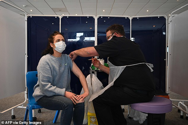 Vaccine age bands are set to be widened, with no priority for key workers, meaning that over-40s could get a first does of a Covid jab by the end of March. Pictured:A vaccinator administers an injection of AstraZeneca/Oxford Covid-19 vaccine to a patient at the vaccination centre set up at Chester Racecourse, in Chester, England, on February 15