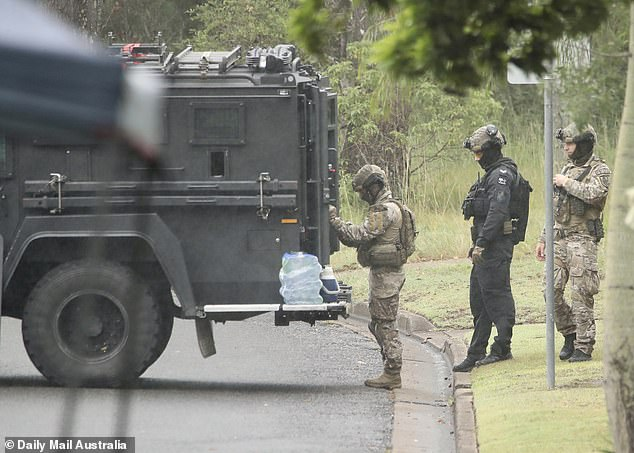 A 'emergency declaration' still remains in place on Friday, 24 hours after the incident. Pictured are tactical police at the scene in Sunnybank on Friday morning
