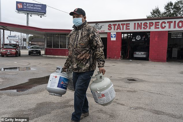Houston, Texas:: A person carries empty propane tanks Thursday, bringing them to refill at a propane gas station after winter weather caused electricity blackouts