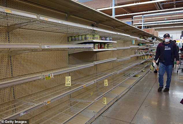 Austin, Texas:shopper walks past a bare shelf as people stock up on necessities at the H-E-B grocery store Thursday.Winter storm Uri has brought historic cold weather and power outages to Texas as storms have swept across 26 states