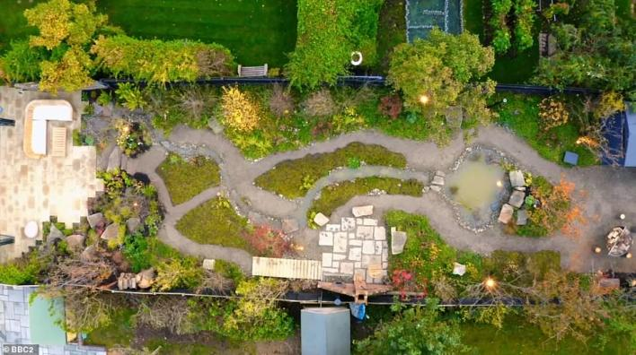 The winning design created a wild oasis of rocky paths, waterways and untamed meadows - and reused the tree, which would've been expensive to remove, to create bespoke furniture. Pictured, after the transformation