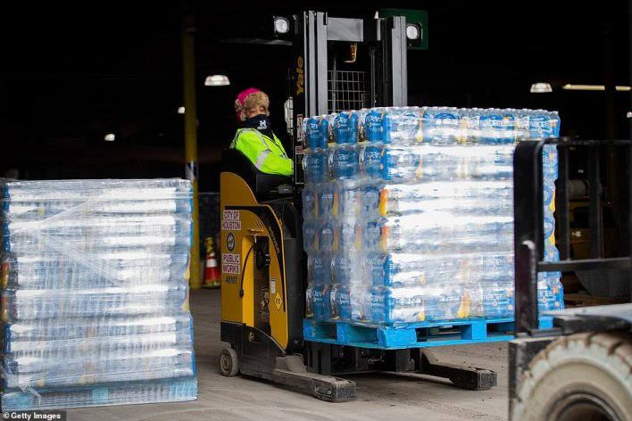 A worker transports bottles of water from the City of Houston Upper Braes Warehouse to delivery trucks