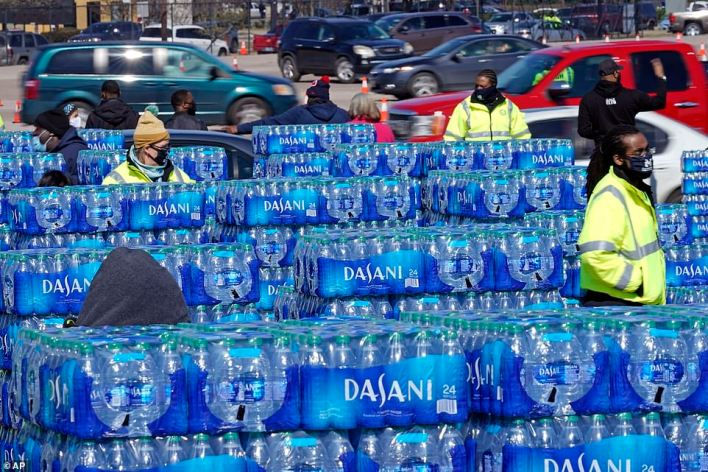 Several city workers are seen amidst piles of bottled water waiting to be distributed to needy residents on Friday