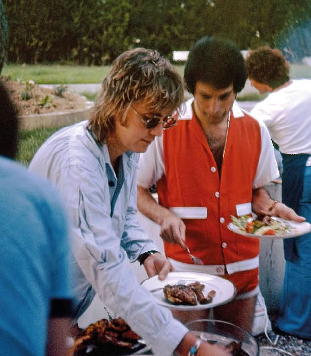 The photograph of Mercury loading up his plate with his Queen bandmate, drummer Roger Taylor, has been shared for the band's 50th anniversary, among other images from Brian May's personal collection