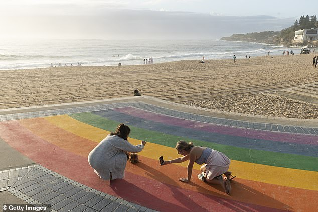 Two women and a dog strive for the ultimate Instagram shot on the Coogee rainbow