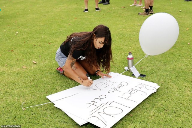 An anti-vaxxer is seen writing up her placard ahead of the march in Melbourne on Saturday