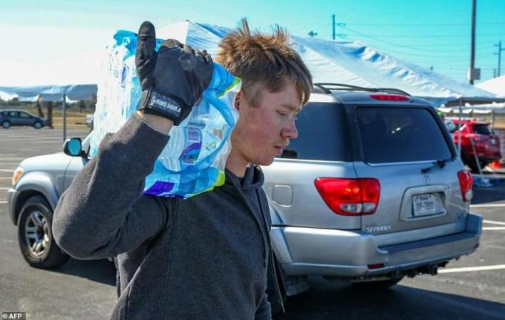 Volunteers hand out cases of water to residents on February 19, 2021 in Galveston, Texas, after a fierce, deadly winter storm