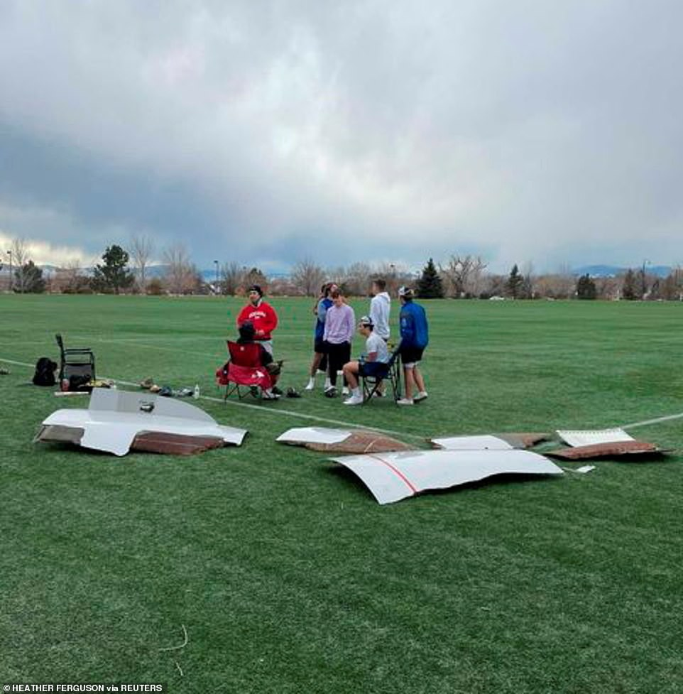 Pieces of debris are seen above on a local football field in Broomfield, Colorado - a suburb located 25 miles north of Denver