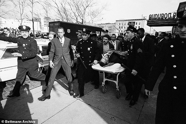 Two policemen carry stretcher bearing Malcolm X after he was downed by an assassin's bullets at a rally