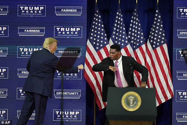 Walker elbow-bumps Trump at a campaign rally in Atlanta on September 25