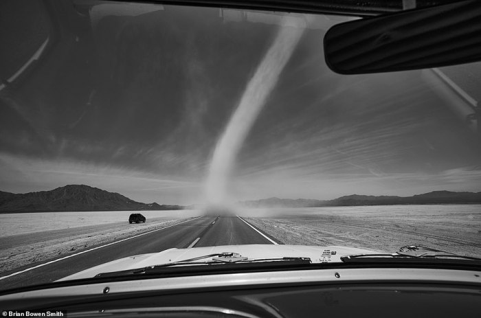 A dust storm is seen upon the horizon as Smith travels across a flat highway in the American west