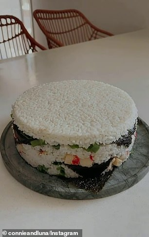 She repeated the step until the tin was full before she flipped cake upside down, placing it on a board. Connie then removed the tin to reveal the sushi cake