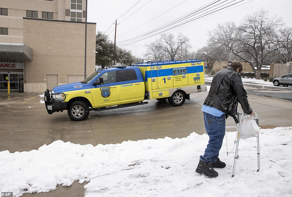 Russell Brown walks away in the snow after being discharged from St. David's South Austin Medical Center in Austin, Texas, on Thursday. Brown was discharged from the hospital that was evacuating some patients after it ran out of water and lost heat