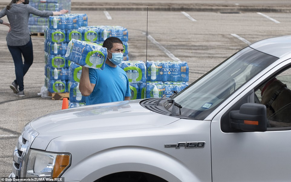 Volunteers including Elie Sierra pass out cases of bottled water to desperate drivers in Travis County, Texas