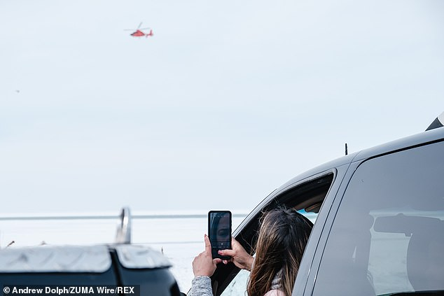 A woman photographs a United States Coast Guard helicopter as people are rescued off the ice of Lake Erie by members of the USCG Ice Rescue Team