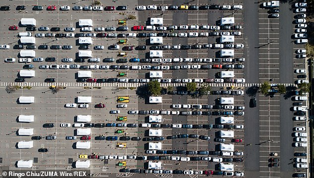 Motorists and passengers wait in line for their Covid-19 vaccinations administered by members of the National Guard at a joint state and federal COVID-19 vaccination site on the campus of California State University of Los Angeles in Los Angeles on Wednesday