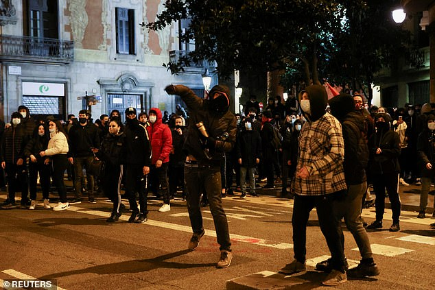 Angry demonstrations erupted on Tuesday after police detained 32-year-old rapper Hasel and took him to jail to start serving a nine-month sentence in a highly contentious free speech case. Pictured: Protesters throw objects at police on Sunday