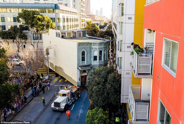 A man watches from a balcony as a truck pulls a Victorian home through San Francisco on Sunday