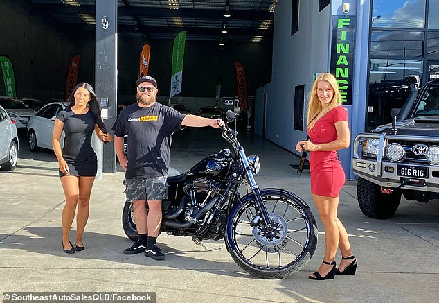 Pictured: A man with a new motorcycle poses for a snap with two of the the sales team's photogenic staff members
