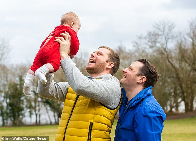 Anthony Deegan (right) with his partner Ray Williams and baby Theo in a local park