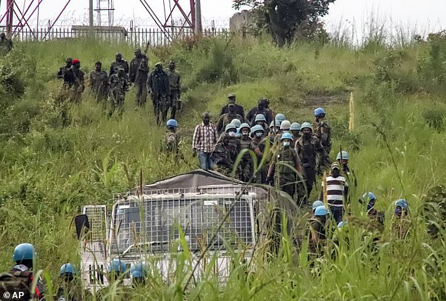 United Nations peacekeepers remove bodies from an area near to where a U.N. convoy was attacked and the Italian ambassador to Congo killed, in Nyiragongo, North Kivu province, Congo Monday, Feb. 22, 2021