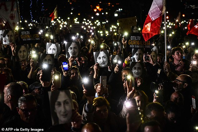 People holding placards and photos of killed journalist Daphne Caruana Galizia stage a protest called by Galizia's family and civic movements outside the office of the prime minister in Valletta, Malta in 2019