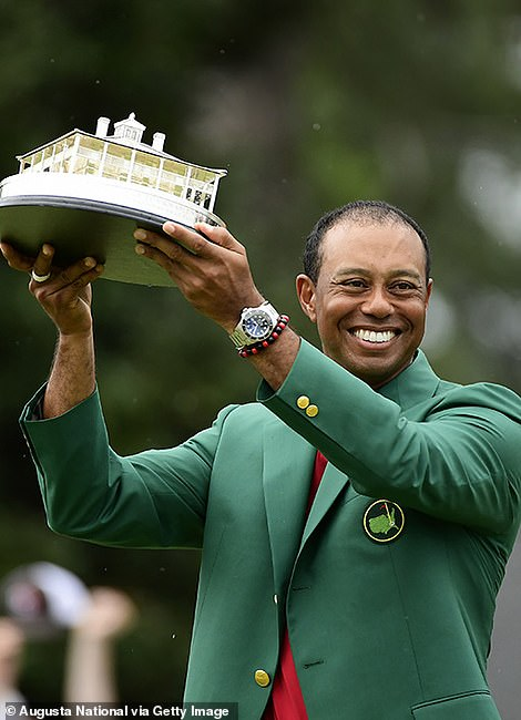 Woods poses with his trophy after winning the Masters at Augusta National Golf Club, Sunday, April 14, 2019
