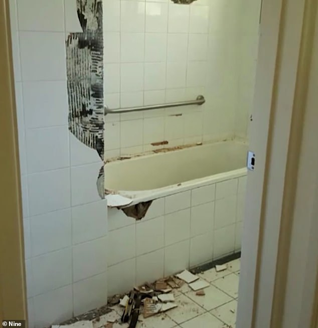 House of horrors: The bathroom tiles were smashed around the old and tired bathtub, while the bay windows were curtain-less and exposed