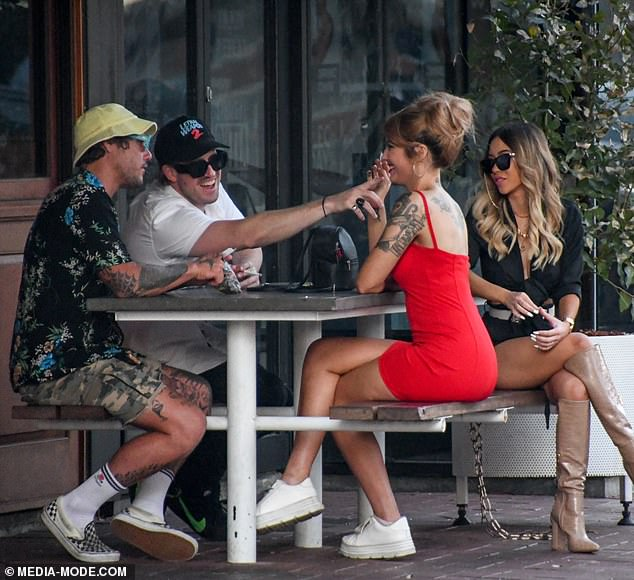 Chilling out: At one point, she could be seen puffing on an unhealthy cigarette while sitting at a table with her friends