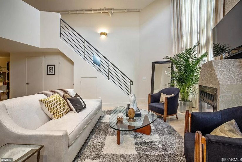 Among the additions Harris has made since she moved in are floor to ceiling drapes, wall paper on the first floor and an air conditioner.Pictured: The living room with stairs leading to the upstairs bedroom