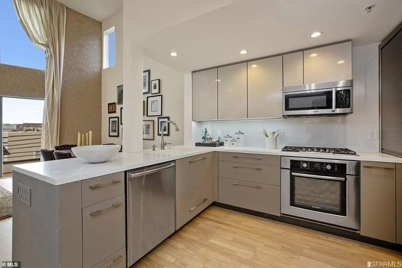 The main level has a living room and a dining room with high ceilings, a chef's kitchen with a gas stove (pictured), a home office alcove and a half bath