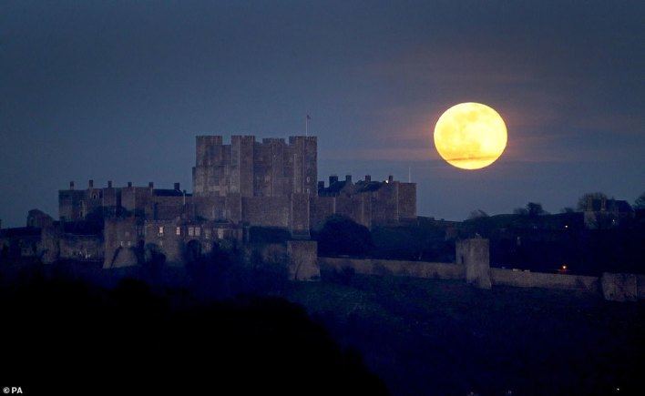 A breathtaking Snow Moon (pictured over Dover Castle in Kent) glowed burning orange over the UK tonight as Britain welcomed its second full moon of 2021