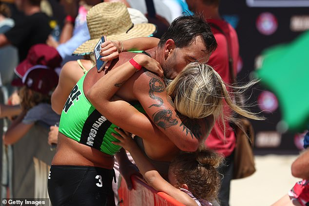 Passionate: The genetically blessed couple got passionate about their lips as Matt crossed the finish line