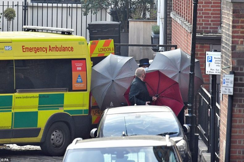 Staff use umbrellas to shield someone getting into an ambulance outside the rear of King Edward VII Hospital in London today