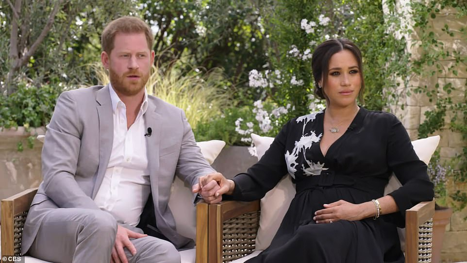 AWKWARD: Prince Harry looks far less comfortable than Meghan in front of the camera