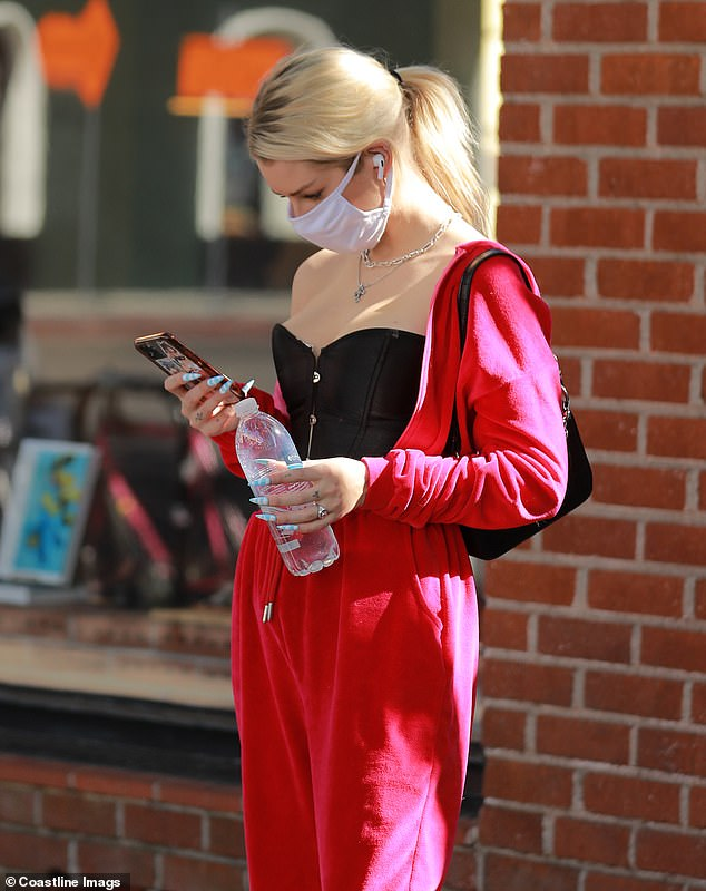 Distracted: She was seen holding a water bottle and a message on her phone