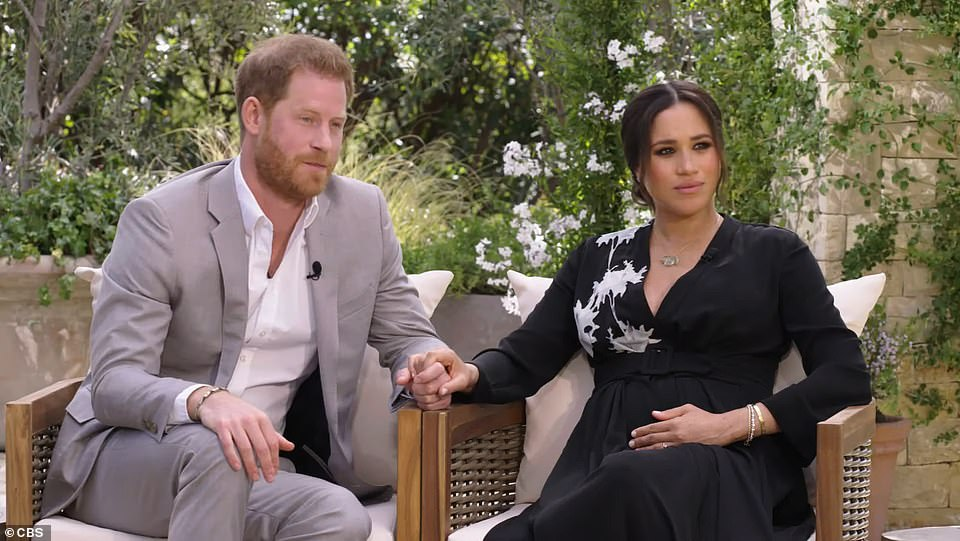 PROTECTIVE OF HARRY: Harry's hand looks balled into a fist beneath Meghan¿s reassuring hand. The Duchess of Sussex also keeps a hand resting on her baby bump