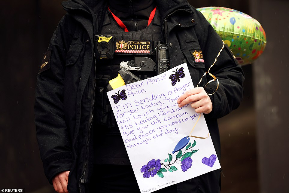 A police officer carries a balloon and a touching message for Prince Philip outside St Bartholomew's Hospital yesterday