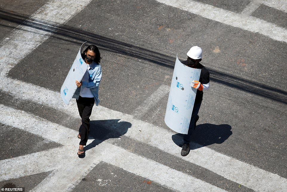 A pair of demonstrators carry shields to the frontlines as they face off against police in Yangon on March 4