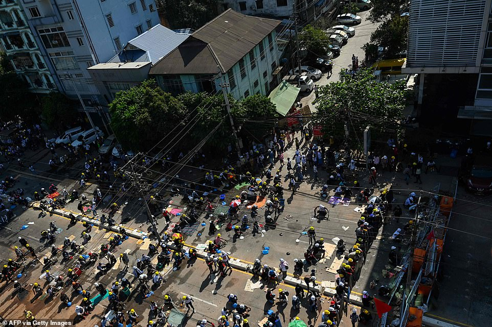 Protesters gather behind a makeshift blockade in a demonstration against the military coup in Yangon on Thursday